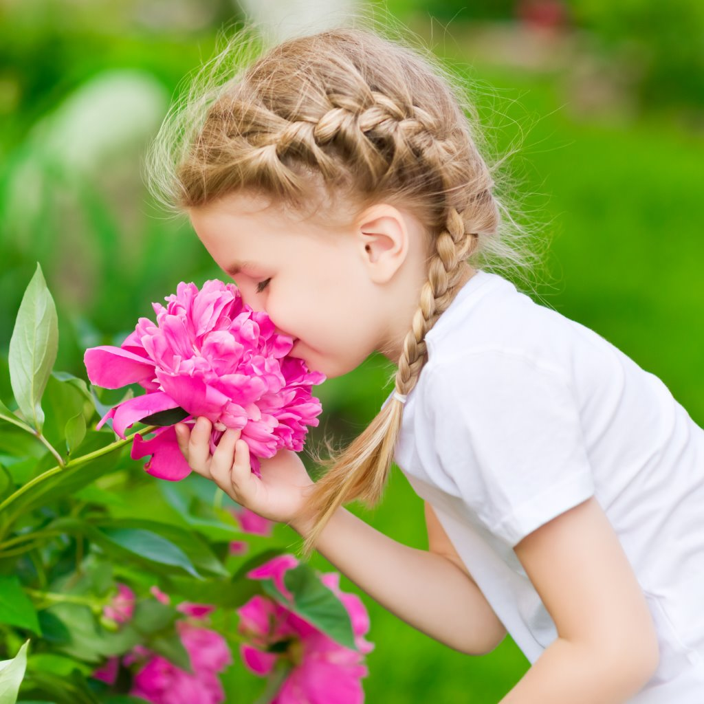 Blonde Girl With Braided Hair Smelling Pink Flower In Garden Picture Id176421749 1